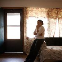 A woman leans against a bed in a dimly lit room.