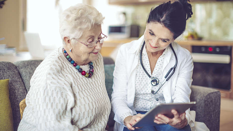 An older women sits next to a doctor holding a tablet