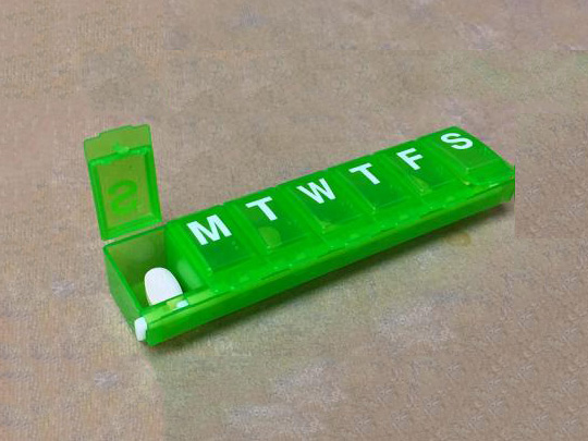 Green pill box with sections for each day of the week.