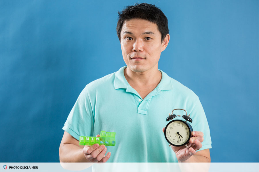 Man holding a container of pills and an alarm clock