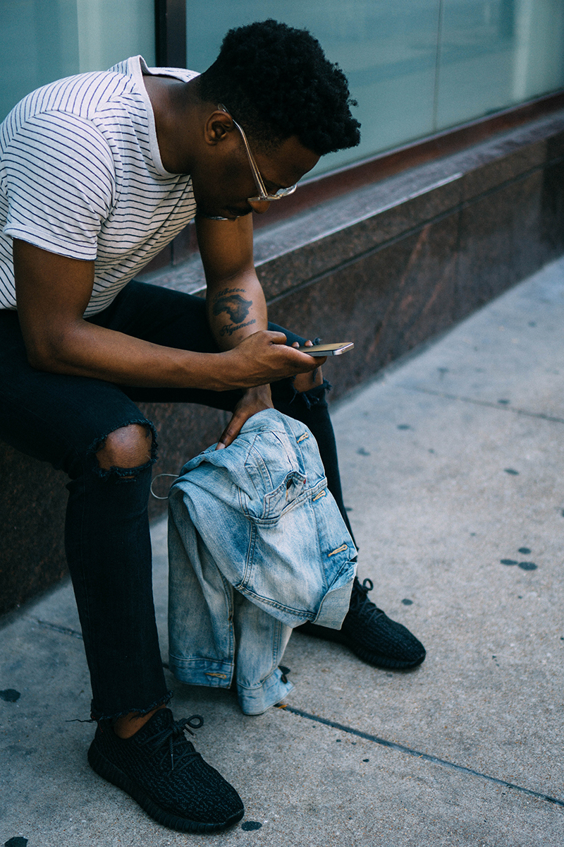 Photo of a man sitting outside looking at his phone.