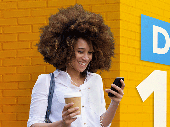 Woman smiling at her phone, holding a cup of coffee