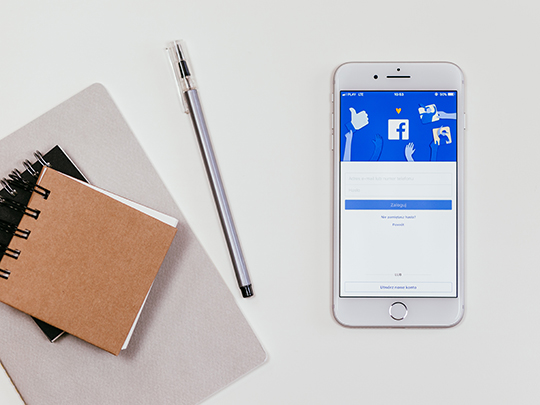 Image of notebooks and a phone showing the facebook log in screen.