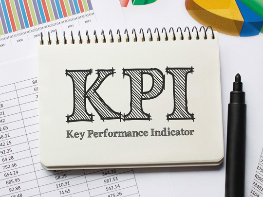 A pad with the words KPI, Key Permformance Indicators with a pen and sitting on a pile of charts and graphs.