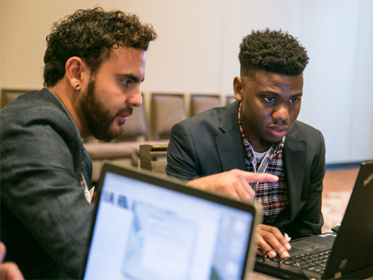 Photo of two mean looking at a computer screen