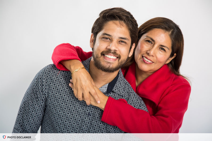 Woman wrapping her arms around a man, both smiling at the camera