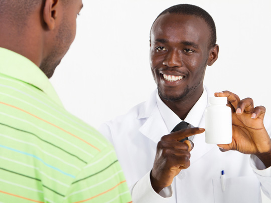 A doctor in a white lab coat holds up an unmarked bottle of medicine to a patient.