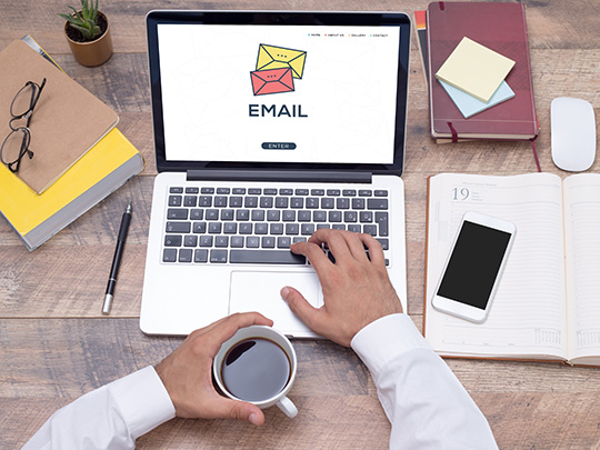 """A laptop sits on a desktop with the word, """"email"""" on the screen and icons of opened and unopened emails floating across the image."""