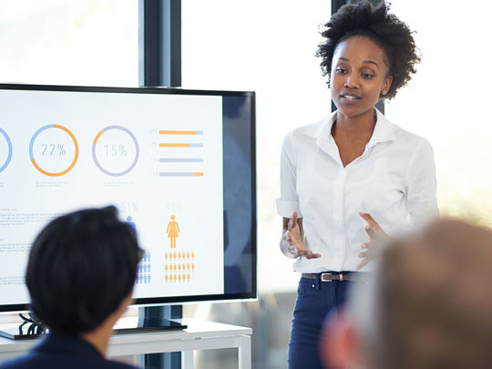 A woman presents metrics to two colleagues