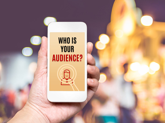 """Photo of a hand holding a smart phone with the words, """"Who is Your Audience?"""""""