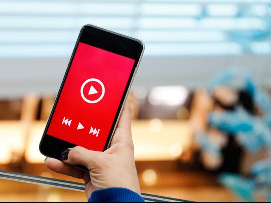 A hand holds a cell phone with a video prepped to play